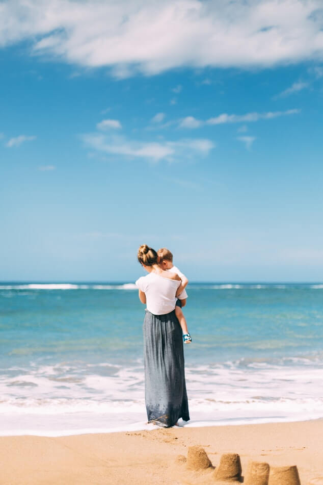 young trendy mother carrying baby at the beach kids' summer fashion